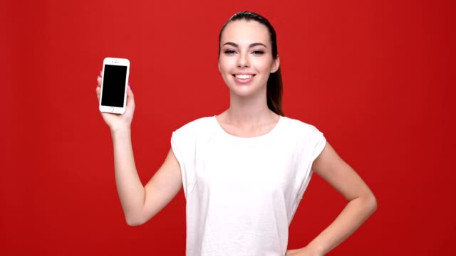 Young cheerful caucasian woman wink and pointing to phone over red background. video