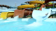 SLOW MOTION: Young cheerful man sliding down the water slide falling into pool in fun aquapark on a hot summer day video