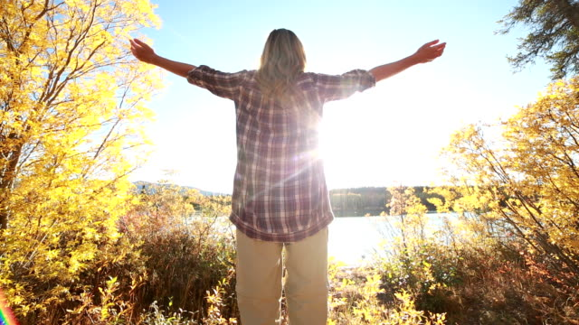 Young cheerful woman arms outstretched in nature video