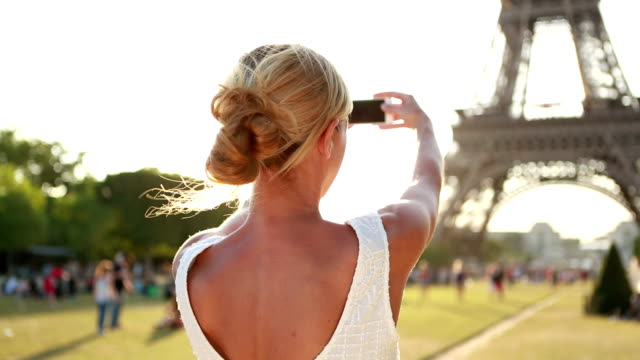 Young cheerful woman at Eiffel tower-Paris, France taking a selfie video