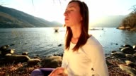 Young cheerful woman by the lake exercising yoga at sunset video