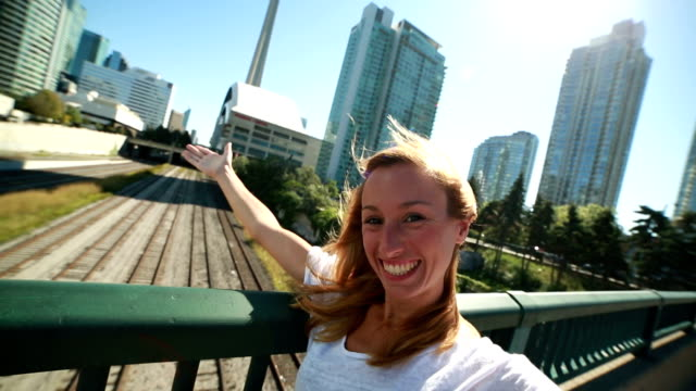 Young cheerful woman in Toronto taking selfie portrait with cityscape video