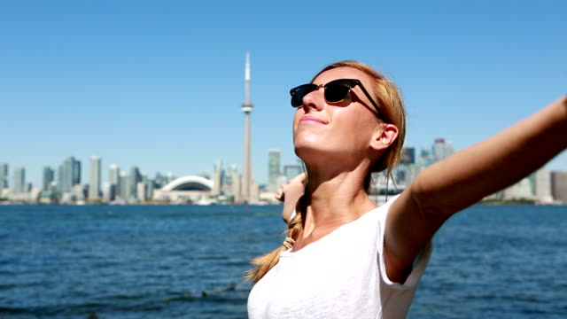 Young cheerful woman in Toronto-Canada arms outstretched video