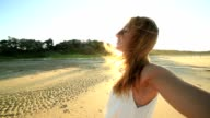 Young cheerful woman on beach arms outstretched for positive emotion video