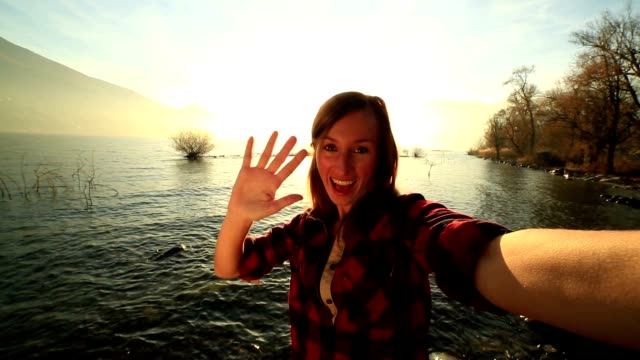 Young cheerful woman takes a selfie portrait by the lake video