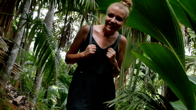 A young cheerful woman waking through a tropical jungle. video