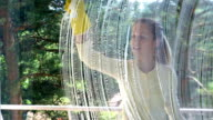 Young cheerful woman washes a window using a special brush and a sponge. video