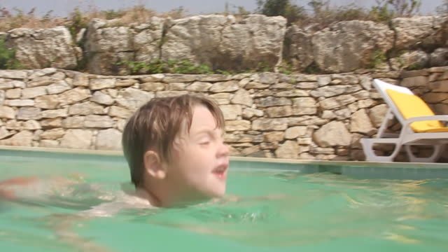 Young child learning to swim outside video