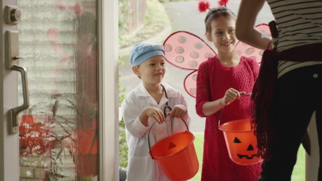 Young children knocking on door trick or treating on halloween video
