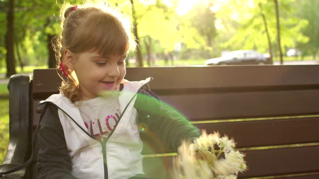 Young children playing with a flower in the Park. video