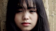 young chinese woman portrait: pensive young asian woman looking in camera video