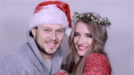 Young Christmas couple enjoying snow over white background. video