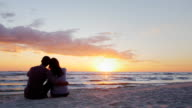 A young couple admiring the sunset at sea. Sit in an embrace on the sand video