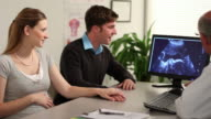 Young couple and a doctor look at an ultrasound video