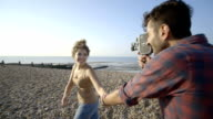 Young couple and camcorder on beach video