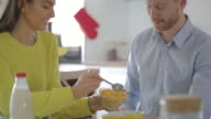 Young couple at home having a breakfast cereal video