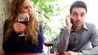 Young couple at restaurant. Boyfriend on mobile phone video
