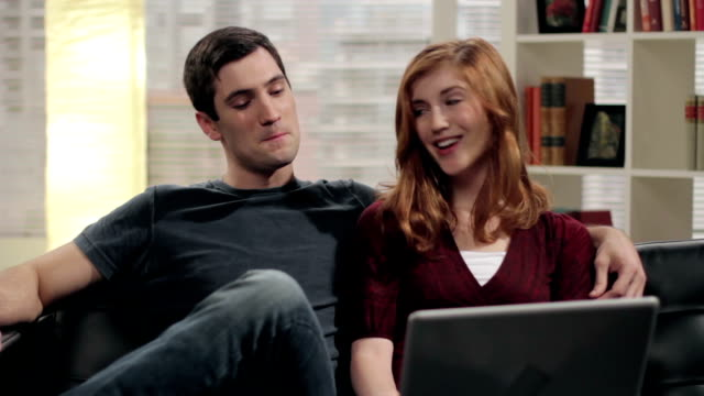 Young couple browsing on a laptop computer video