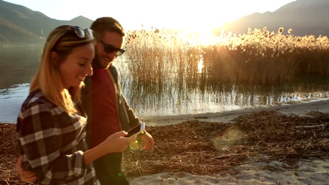 Young couple by the lake text messaging on phone video