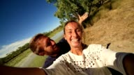 Young couple by the river take a selfie portrait video