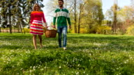 Young couple carrying picnic baskets in park video