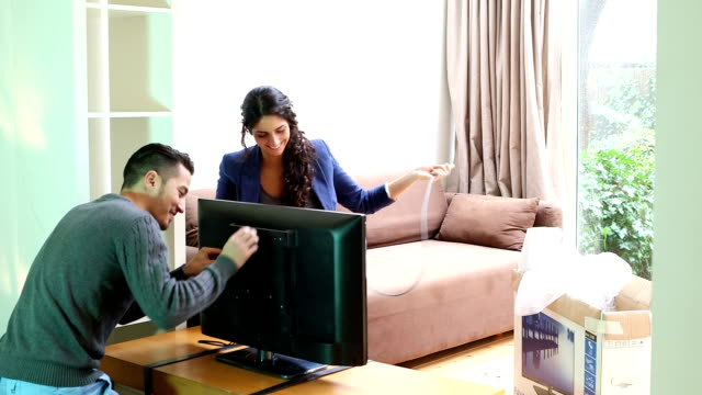 Young couple connecting cable to new television video