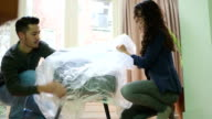 Young couple covering new chair in plastic video