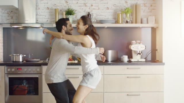 Young Couple Dances in the Kitchen then Girl Flirtatiously Jumps in Man's Arms. video