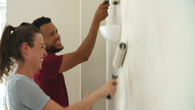 Young couple decorating home with paint rollers, close up video