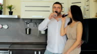 Young couple drinking red wine in the kitchen at home video