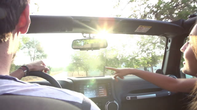 Young Couple Driving Along Country Road In Open Top Car video