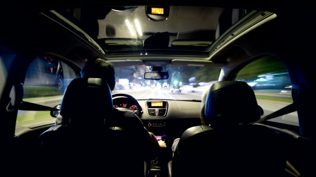 Young couple driving in a car through city at night video