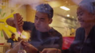 A young couple eating burgers and fries at a restaurant, through the window video