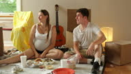 Young couple eating on the floor of their new home video
