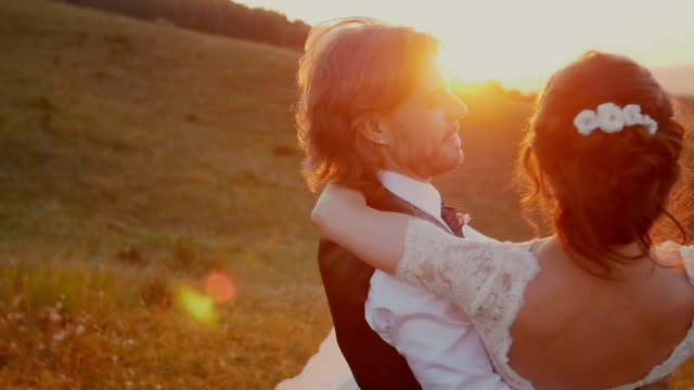 Young couple embracing and whirling at sunset . video