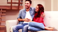 Young couple embracing on sofa video
