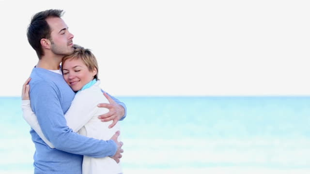 young couple embracing on the beach video