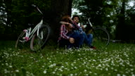 HD: Young couple enjoy break after riding bicycle outdoors. video