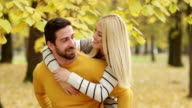 Young couple enjoying in park in autumn video