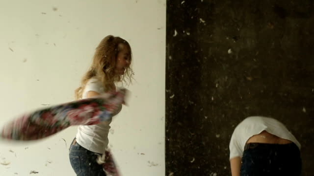 Young couple fighting pillows in the studio video