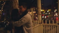 A young couple flirting on a porch in the city at night video