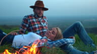 Young couple having a campfire in nature at night video