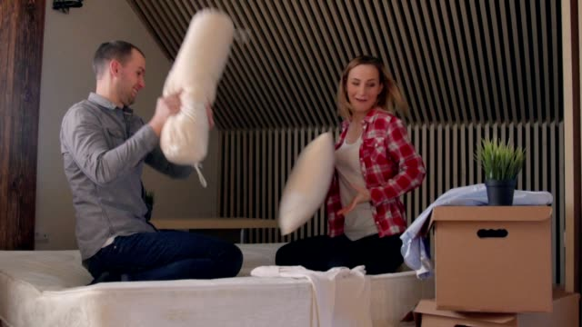 Young couple having a pillow fight in a home bedroom video