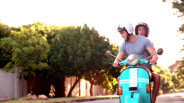 Young couple having a road trip together on their scooter video
