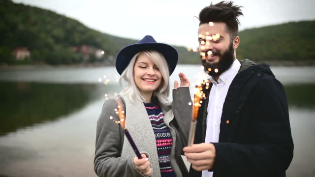 Young couple having fun and celebrating life, holding sprinkles and smiling video