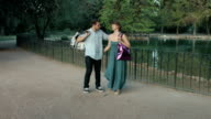 young couple having fun in a park making jokes after shopping: shopping bag video