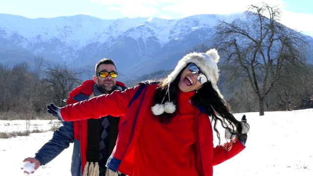 Young couple having fun in snow mountain-slowmotion video