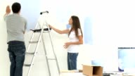 Young couple having fun while they painting a wall video