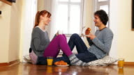 Young couple having snack at home, enjoying their love and marriage video