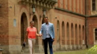 Young couple having summer walking near old univercity building video